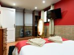 The red bedroom with double bed and TV