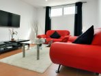Stunning red furniture in the lounge which has a 42 inch TV