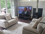 Open plan lounge with 65 3D TV Bluray player Xbox 360 IMac leather sofas and woodburner