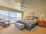 The master bedroom is adorned with floor-to-ceiling windows overlooking the bay and a plush king-sized bed.