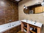Planta principal. Baño con bañera de hidromasaje, lavabo de dos senos y ducha de Casa Salva
