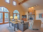 Cathedral ceilings, beautiful arched windows,  and a stone wood-burning fireplace create a warm and inviting...