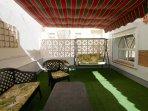 Terraza con césped artificial y toldo.