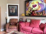 The host welcomes visitors to join in the living room area to watch television and enjoy her art