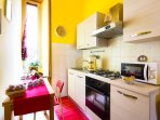Kitchen with pots, plates, glasses, cutlery, kettle, gas oven, microwave, salt, coffee, oil, sugar