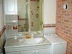 La salle de bain, son meuble lavabo à miroir et le lave linge