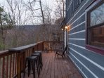 Main level deck w/bar table overlooking mountain views or to use with the BBQ.