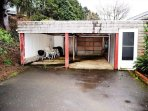 Carport with patio table, chairs and a charcoal BBQ