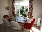 Dining table and chairs in living room overlooking front garden