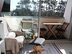 Balcon exposé plein sud ensoleillé avec vue sur les pins, table, chaises et barbecue électrique