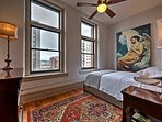 Enjoy beautiful artwork, a plush queen bed, and mesmerizing city views from the cozy bedroom.
