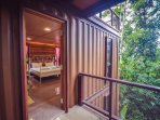 The container house's surroundings are natural and green.