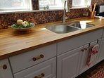A sunny kitchen with butcher block counter top.