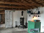 Dining table with four chairs. Hutch with pots pans, silverware & plates. Pot belly wood stove