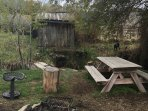 Campfire ring, chairs, picnic table,electric outlet, water spigot, propane BBQ grill are creek side