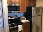 The kitchen has quartz counter tops and stainless steel appliances.