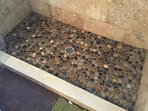 Your tired feet will be massaged by the river rock shower floor