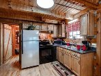 Kitchen features stainless fridge, new stove, new countertops, & open floorplan.