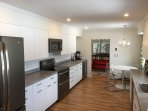 Fully equipped kitchen with new range, refrigerator, dishwasher, and double beverage cooler.