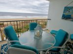 Outdoor  table with four chairs and lounge chair create a beautiful ocean front sitting arrangement