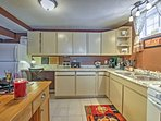 The well-equipped kitchen area is complete with an adorable wooden island eating area and granite countertops.