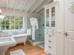 Master bath has a claw-foot soaking tub and a large frame-less glass enclosed shower with a view.