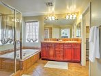 This spacious bathroom features a double vanity, large tub, and walk-in shower.