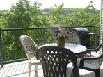 Private lakeside covered balcony with table, chairs and gas grill. Condo 2.