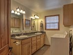 This bathroom features a double vanity and in-unit laundry machines.
