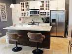 Fully equipped kitchen with stainless steel appliances and additional seating at the kitchen counter for 2.