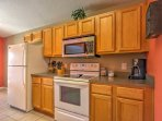 This brightly colored kitchen comes fully equipped with all the essential cooking appliances.