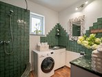 Bathroom with shower and washing machine at ground floor