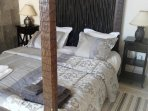 Bedroom 2 with four poster bed. Opens onto pool deck