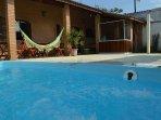 Rede de balançar ao fundo rasteirando pela piscina.