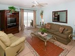 Tiled living room with sofa, recliner, ceiling fan and access to Gulf-front balcony