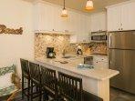 Cucina, che comprende elettrodomestici in acciaio inox, lavastoviglie e frigorifero con ice maker.