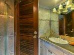 bagno al piano inferiore splendidamente piastrelle in tutto con pavimento in pietra sotto la doccia