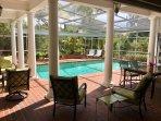 Screened heated pool and lanai overlooking yard and lake.