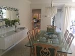 Dining area leading to kitchen, pool and master bedroom.