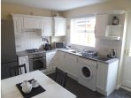 Spacious well equipped kitchen with breakfast table and chairs overlooking the garden area.