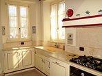 Cucina, ampio lavello in marmo, fornelli a gas, cappa con aspiratore.