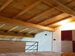 Camera sul soppalco. Soffitto in legno a vista. Cassettiera.