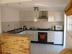 Kitchen with granite work tops. Microwave, cooker, washing machine, kettle etc. Tea,coffee and sugar