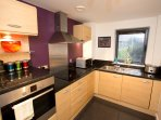 The fully-fitted kitchen includes, large fridge-freezer, hob, oven, dishwasher and washer/dryer
