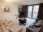 The spacious lounge easily accommodates four people, including a large dining table and kitchen