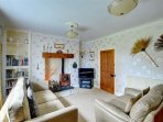 The comfortable sofas are placed in front of a woodburning stove and flatscreen TV