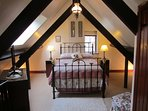 Upstairs gallery bedroom with antique Victorian double bed.
