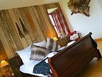 Kingsize bedroom with reclaimed wood walls and ensuite bath and shower