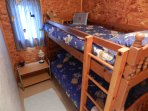 The bunkbed room decorated for kids. There is a selection of games and books.