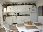 Fully equipped kitchen with refrigerator, 4 burner stove, pots and pans and dishes.